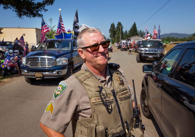 Lane County Sheriff Sgt. Scott Denham keeps an eye on an illegal parade as it stages near Creswell on the Fourth of July. Participants were warned not to block traffic, but Denham said he and his officers would spend their patrol time making sure everyone was safe Sunday and pursue any citations after an investigation.