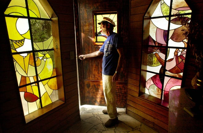Sculptor Howard Solomon peeks out the door of his castle. He hand crafted Solomon's Castle and its 80 stained glass windows.