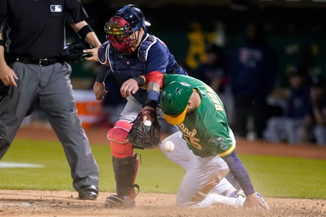 Oakland Athletics' Seth Brown, right, scores past Boston Red Sox catcher Christian Vazquez for the winning run during the 12th inning Saturday night Oakland, Calif.