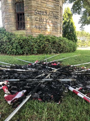 """A burned pile of ashes from American flags burned near the bell tower, with spray painted words """"Separating Church and State"""" on the tower wall at Forest Lawn Cemetery on U.S. Highway 29 in Anderson County on July 4, 2021."""