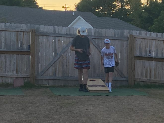 Brock Beasley, right, throws during a game of cornhole at Main Street Grill on Saturday, July 3, 2021.