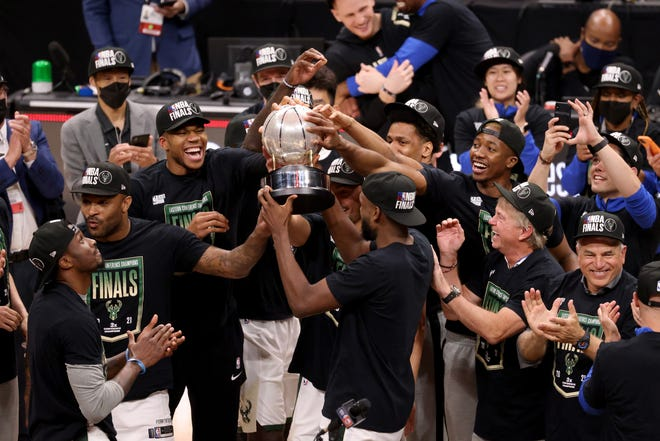 Jul 3, 2021; Atlanta, Georgia, USA; Milwaukee Bucks forward Khris Middleton (22) holds up the Eastern Conference Finals Trophy and celebrates with teammates after the Bucks defeated the Atlanta Hawks in game six of the Eastern Conference Finals for the 2021 NBA Playoffs at State Farm Arena. Mandatory Credit: Jason Getz-USA TODAY Sports