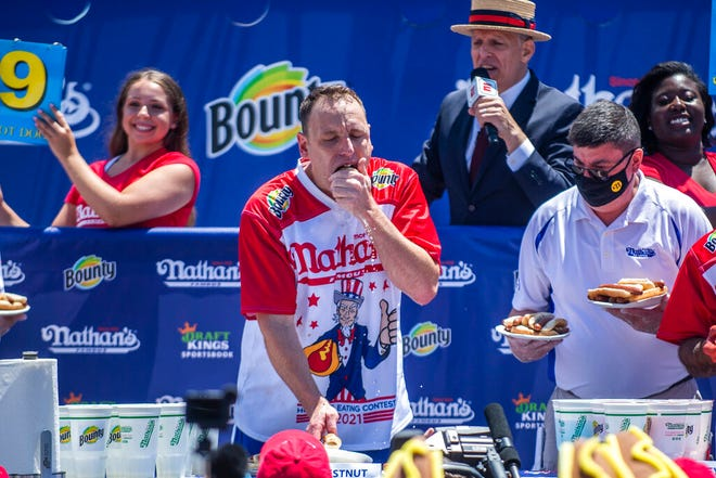 Joey Chestnut, center, competes in the Nathan's Famous Fourth of July International Hot Dog-Eating Contest in Coney Island's Maimonides Park on Sunday, July 4, 2021, in New York. (AP Photo/Brittainy Newman)