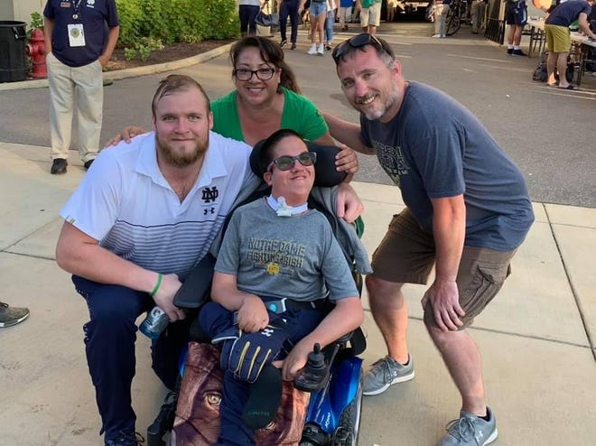Florida State offensive lineman Dillan Gibbons (pictured here while he was attending the University of Notre Dame) with Timothy Donovan and his mother, Paula, and father, Tim. Gibbons in July started a GoFundMe that will make it possible for Donovan, who has a rare medical condition, to attend the Seminoles' season-opener vs. Notre Dame on Sunday nght.