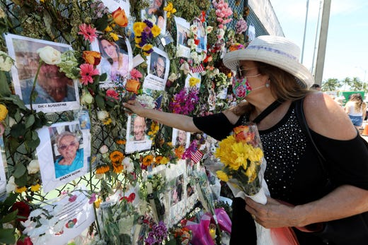 Karol Casper of Miami places a flower near a photo of her friend Linda March, a resident of the Champlain Towers South condo that collapsed last week. Casper was paying her respects at a memorial wall set up near the site of the partially collapsed condo July 4, 2021. March, who moved to the condo three months ago from New York, is among the missing residents of the building.