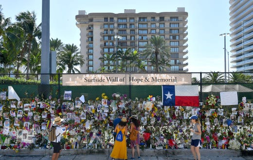 Near the site of the Champlain Towers South condominium collapse is a memorial wall for people missing in Surfside, Fla.