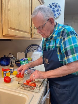 Tom Snyder slices tomatoes for fish.
