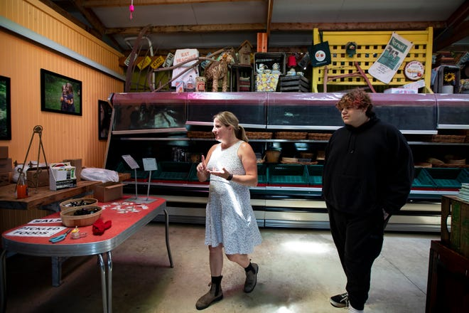 Cindy Zaino, left, shows Eithon Holland, 17, around the Branstool Orchards Market as he gets oriented to work at the market for the summer in Utica. Branstool has seen a large increase in customers during the pandemic.