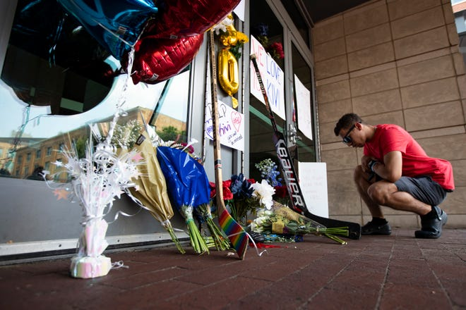 Derek Slane inspects the shrine fans are leaving outside the East doors to Nationwide Arena in Columbus, Ohio in honor of Columbus Blue Jackets goaltender MatissKivlenieks July 5. Kivlenieks was killed Sunday in a fireworks incident in Michigan.