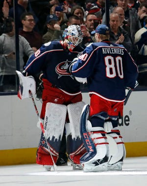 Columbus Blue Jackets goaltender Matiss Kivlenieks (80) congratulates goaltender Elvis Merzlikins (90) on his fourth shutout of the season with a 1-0 win over the Florida Panthers during the NHL hockey game at Nationwide Arena in Columbus on Wednesday, Feb. 5, 2020.