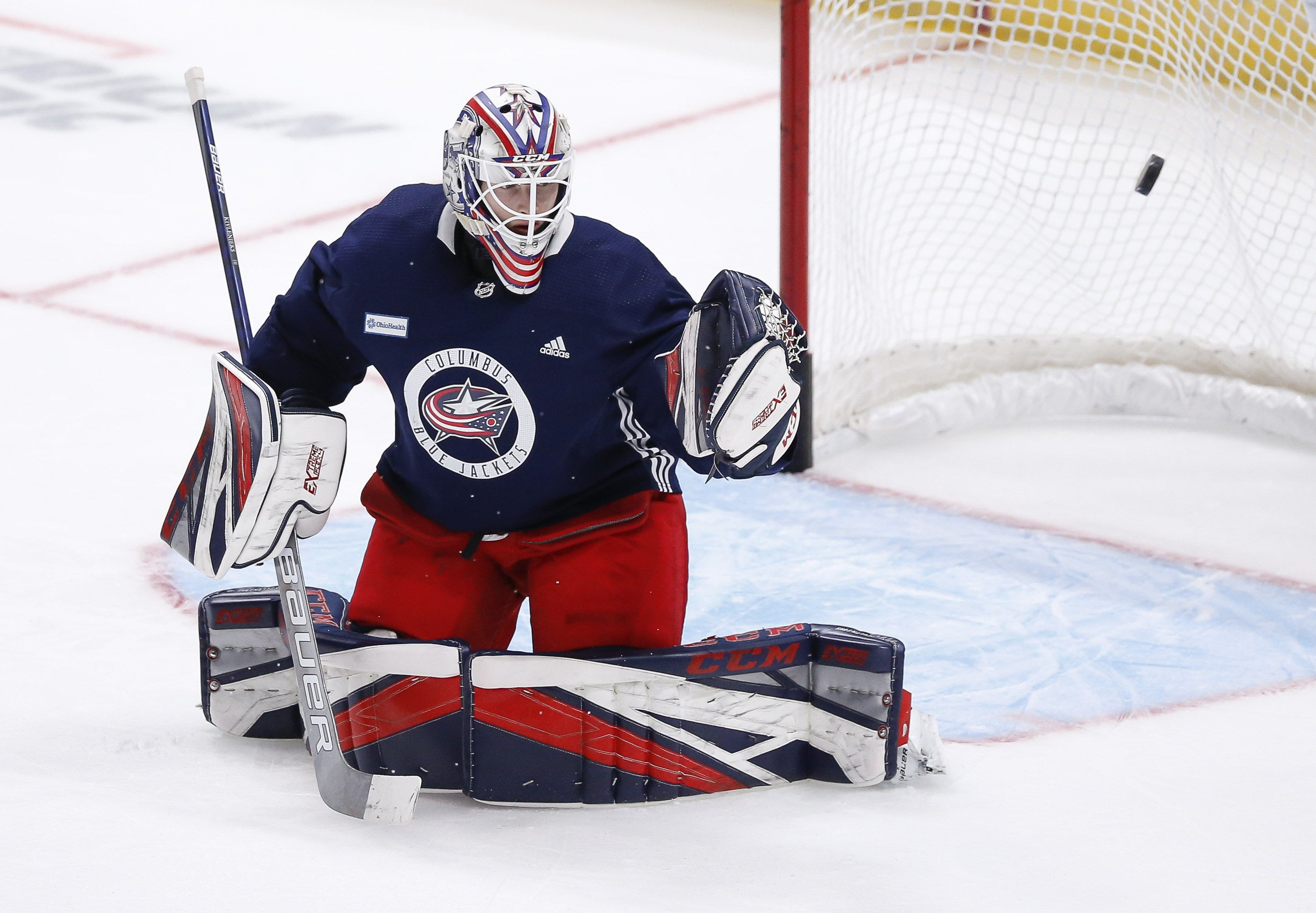 Columbus Blue Jackets goaltender Matiss Kivlenieks (80) deflects a shot during the first day of NHL training camp at Nationwide Arena in Columbus on Monday, Jan. 4, 2021.