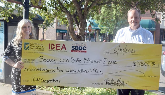 Kelly Van Ert, creator of the Secure and Safe Shower Zone, accepts her check from Mic McCrory with the IDEA Competition.