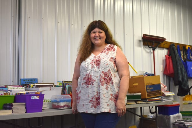 """Connie Mills is pictured at her home next to school items saved through the years. She has a table's worth of saved school items and others boxed throughout the garage and the basement. """"It's a lot of memories worth of teaching at Blissfield,"""" she said."""