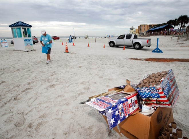 Volunteers collect trash along the beach in New Smyrna Beach, Monday, July 5, 2021.