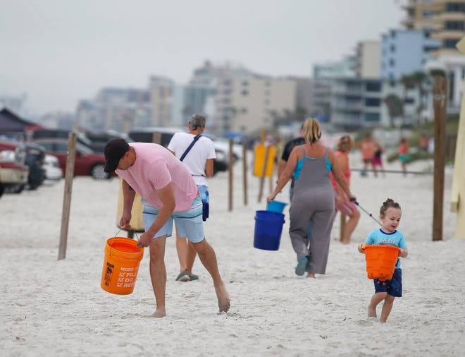 Dustin Bell and his 2-year-old son, Davidson, are two of many volunteers who gathered to collect trash along the beach in New Smyrna Beach this summer.