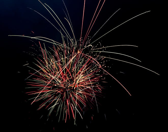 Fireworks light up the sky over the Arkansas River bed Sunday during Garden City's annual Fourth of July fireworks display. For the first time in many years, the show began before dusk this year.