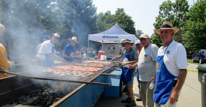 """It was a hot job in the 90-degree temperatures Sunday, July 4, in Geneseo City Park, but somebody had to do it and Jim Unrath, at left; and Dick Baum and Dean Yoder, at right, were among the """"chefs"""" who stepped up to grill the pork chops for the Geneseo Kiwanis Club's annual """"Pork in the Park."""""""