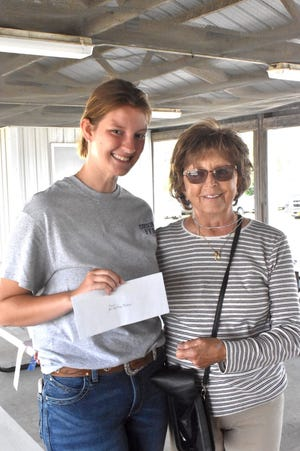 Sydney Perkins, left, of Orion FFA receives the Dallas DeShane Scholarship at the Section 3 FFA fair on Friday, July 2, at the Henry County fairgrounds in Cambridge. Roxie DeShane, right, presents the scholarship in memory of her late husband to someone interested in horticulture, floriculture or an ag-related career. Perkins is a 2021 graduate of Orion High School. She plans a career as a large animal veterinarian