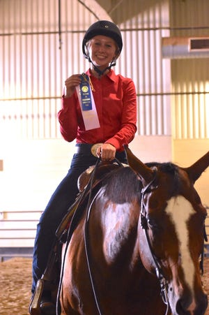 Violet Hodgson of Geneseo FFA displays the reserve grand champion ribbon she earned in the pleasure riding division of the Section 3 horse show on Thursday, July 1, at Black Hawk College, East Campus, Galva.