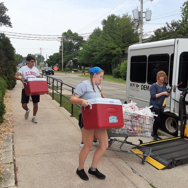 AmeriCorps Vista member Willow Mcilvaine-Newsad and volunteers loading food.