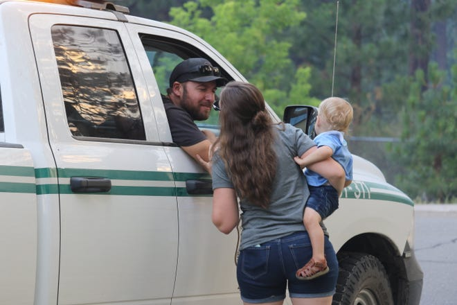 Mount Shasta's Lindsey Moglia gives her husband, Kevin Moglia, a kiss goodbye as he heads out to fight the Lava Fire Sunday evening, July 4, 2021. Kevin, a firefighter with the U.S. Forest Service in McCloud, is working nights and has been able to return home to sleep during the day, said Lindsey. Also pictured is 16-month-old Colton.