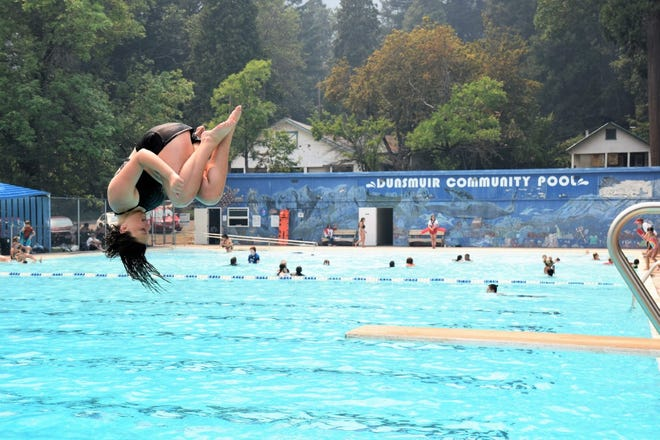 Dunsmuir teenager Yosha Villegas summersaults through the air only to splash down in the cool water at Dunsmuir Community Pool. Many people came to cool off from the heat and the smoke on opening day, July 1, 2021.
