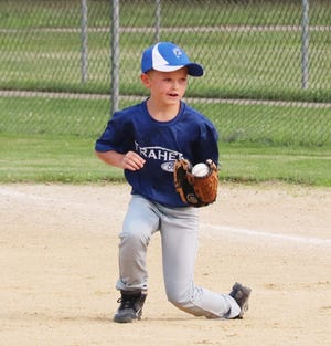 Fraher Ford first baseman Kye Metz fields a ground ball during the Peanut League championship game Friday. Fraher Ford won the game 5-3.