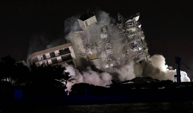 The still-standing portion of Champlain Towers South is imploded Sunday night, July 4, 2021.