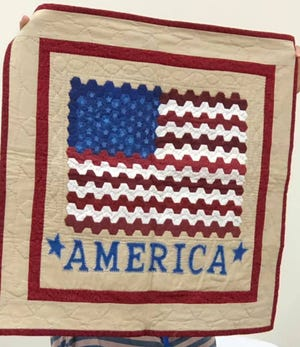 A member of the Pratt Area Quilting Guild shows a patriotic-themed quilt at a recent meeting.