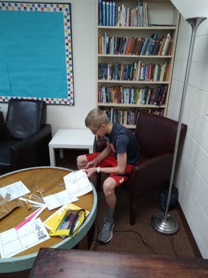 Tucker Lauffer gets busy with paper and scissors during a WWII class last week at Skyline Schools.