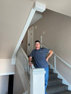Terry Williamson, TK Handyman Services, stands in the hallway of a newly remodeled apartment building in Pratt.