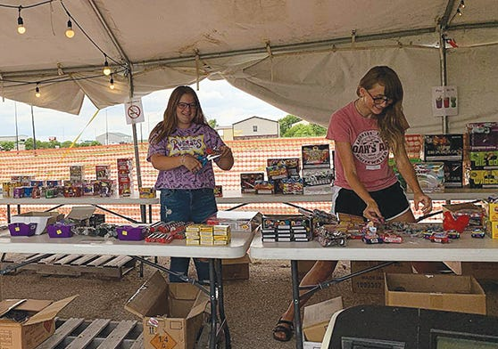 Kenzie Phye (left) and Madi Sullivan (right) arrange fireworks products for sale at the Youth Core Ministries booth in Greensburg.