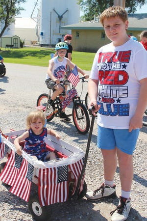 Leo Goodnight (in the wagon) and Caden Parker (pulling) are ready to celebrate the Fourth of July holiday in Iuka as part of that town's first-ever American Pride parade on Saturday.