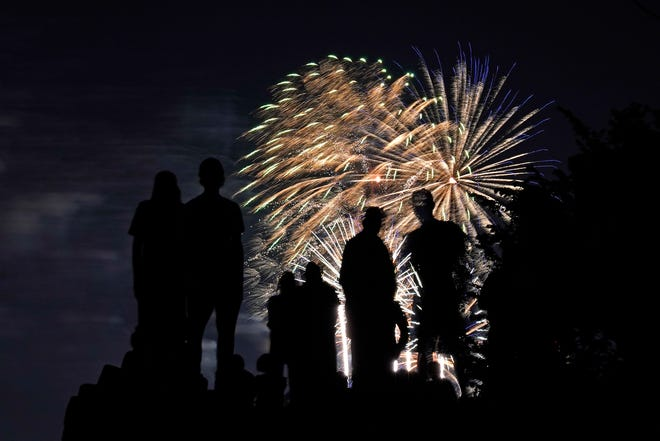 People are silhouetted against fireworks as they watch a Fourth of July celebration from a park in Kansas City, Mo., Saturday, July 3, 2021. AP Photo/Charlie Riedel