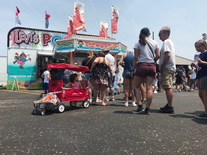 Fair-goers stand in line for tickets to rides on the midway at the St. Joseph County 4-H Fair on Sunday, July 4, 2021.
