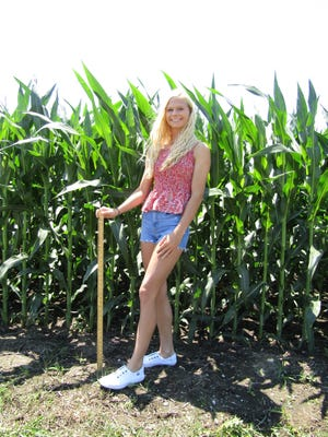 Daci Hier stands 5 feet 5 inches tall in a field on her father, Dan's farm southwest of Kewanee, where she measured this year's corn crop at 6 feet 7 inches, a height that received a much needed boost from almost daily rains in the last 12 days of June.