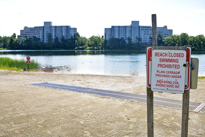 Bell Pond was quiet Monday morning, after a lifeguard was stabbed there Sunday. The beach will be closed Monday.