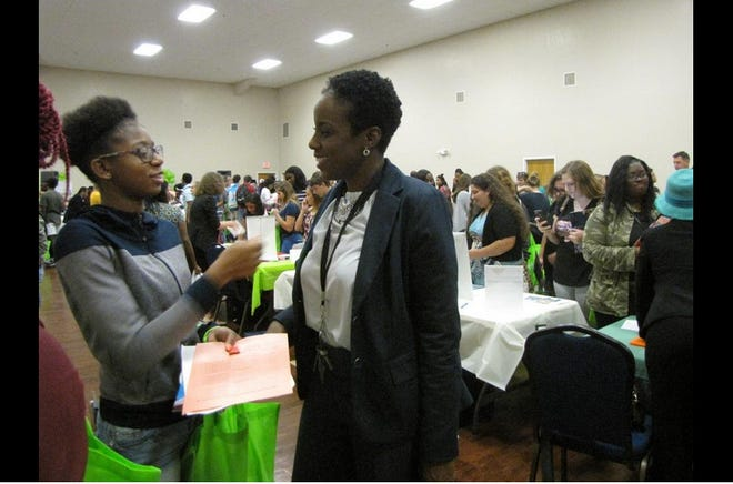 Anntwanique D. Edwards, Ph.D., right, has been named Chief of Equity, Inclusion and Community Engagement with the Alachua County School District. She is pictured here talking to Calisia Woods, then a senior at Eastside High School, during a college fair in 2018. Edwards was an assistant principal at Eastside at the time.