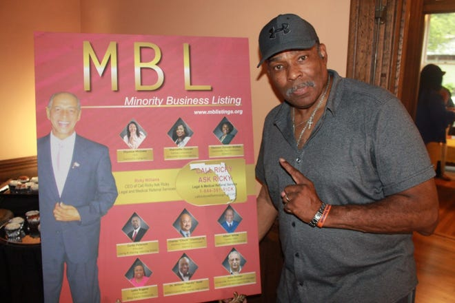 Wayne Fields, CEO and founder of Minority Business Listings, poses in front of a replica of MBL magazine's 4th edition during the grand opening of MBL's cultural center located at 15 SE Seventh St. on Friday.