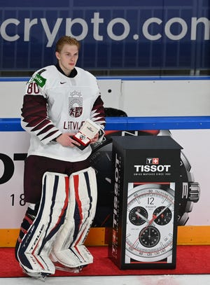 """Latvia's goalkeeper Matiss Kivlenieks holds his award as """"Best Player of the Game"""" the IIHF Men's Ice Hockey World Championships preliminary round group B match Canada vs Latvia, at the Arena Riga in Riga, on May 21, 2021."""