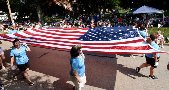 """Park National Bank employees carry a large flag in the """"Mile-Long Parade"""" on Monday in Granville. The city wrapped up the 4th of July Celebration with return of the parade through downtown. The theme for the parade was """"Land That I Love."""""""