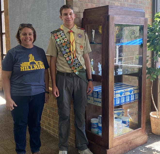 Hillrise Elementary Principal Karin Hite and Scout Liam Rutherford stand next to the trophy case Liam built for the school, his Eagle Scout project.