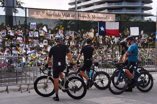 A cycle club takes a moment to stop on their ride through Surfside to take in the Surfside wall of Hope and Remembrance early Monday, July 5, 2021.