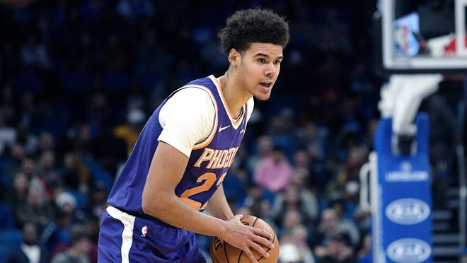 Phoenix Suns' Cameron Johnson (23) sets up a play during the first half of an NBA basketball game against the Orlando Magic Wednesday, Dec. 4, 2019, in Orlando, Fla.