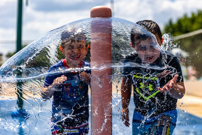 Major Camp, left, and Dax Parrett cool off in the Sooner Park Splashpad on Tuesday. The splash pad, adjacent to Sooner Park swimming pool, is free to the public and open from 9 a.m. to 9 p.m.