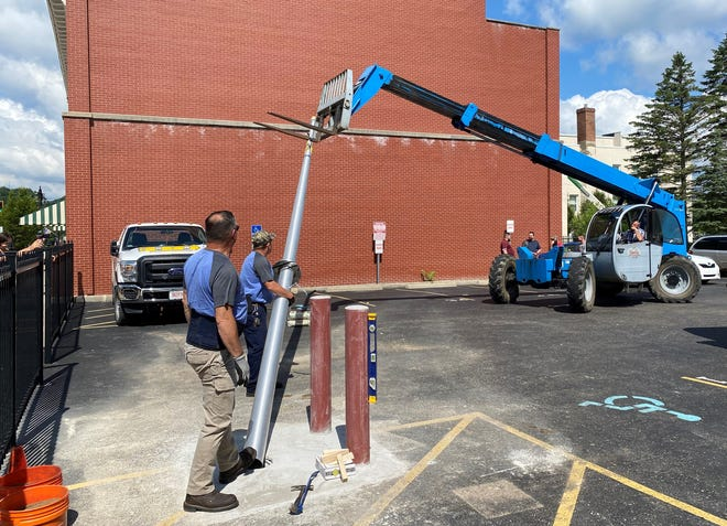 Maintenance employees Eric Robertson, left, and Dan Burton assist David Morrow of Saup Hartley with installation the flagpole for the Guernsey County Veterans Services in the parking lot adjacent to the County Administration building. Cost was approximately $4,000. Saup Hartley donated the services of Morrow and the lift to assist the county. Site preparation work was done by Jack Warne Construction. Guernsey County commissioners also assisted with the project.