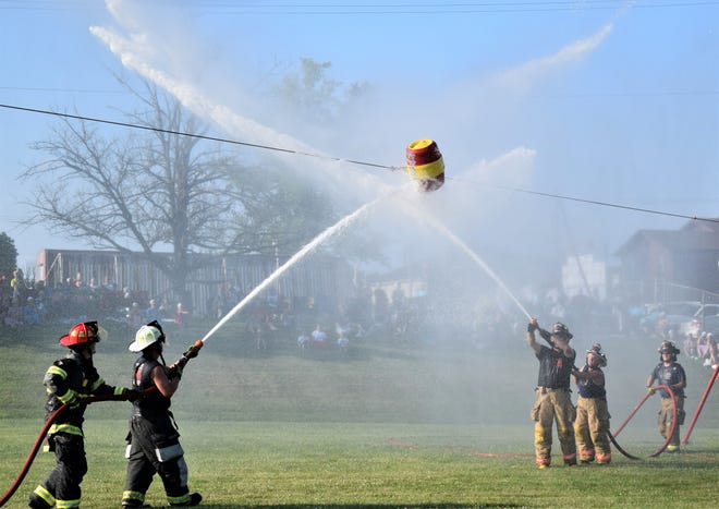 Firefighters from Apple Creek (left) and West Holmes battled it out on the field behind Berlin Elementary School during last year's barrel blast at the East Holmes Firemen's Festival. This year's event is scheduled to begin at 4 p.m. Saturday, July 17.