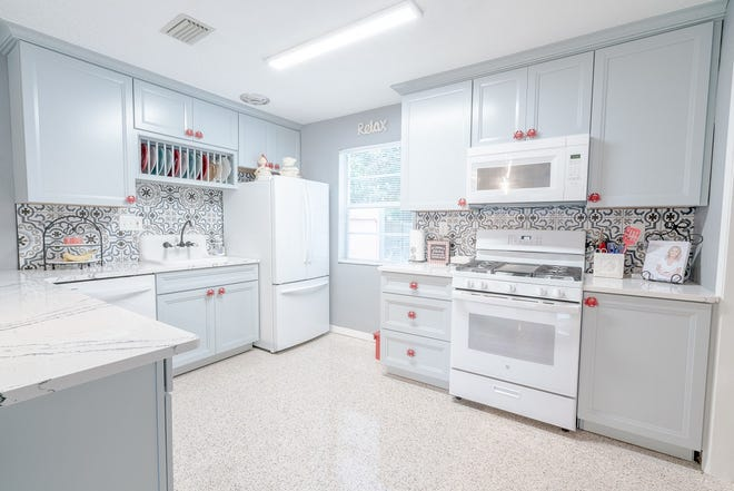 The kitchen has been updated with beautiful marble-patterned Corian countertops, oversized tile backsplash, craft-made cabinets, soft-close drawers, a China rack above the sink, white appliances and a gas stovetop, with a built-in griddle.