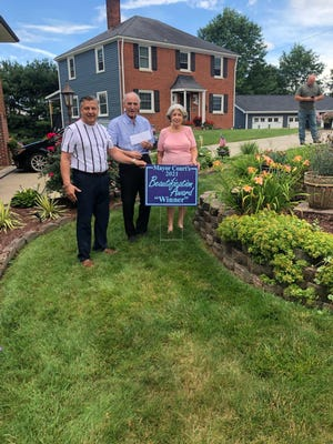 """Ellwood City Mayor Anthony Court (left) announced the fourth winner of his 2021 Beautification Award, being John and Kelly Katsadas. """"Congratulations on a job well done. Looks Great,"""" said Court. The Katsadas were presented with a yard sign to display and a gift certificate from a local restaurant. There will be two more winners for 2021."""