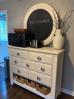 This dresser/mirror was transformed into a kitchen buffet by Michelle Hannold, owner of Purposely Repurposed by Michelle. The mirror was repurposed into a chalk board and the handles were replaced to match the cabinet drawers. The project illustrates what a little paint, creativity, and thinking outside the box can accomplish.